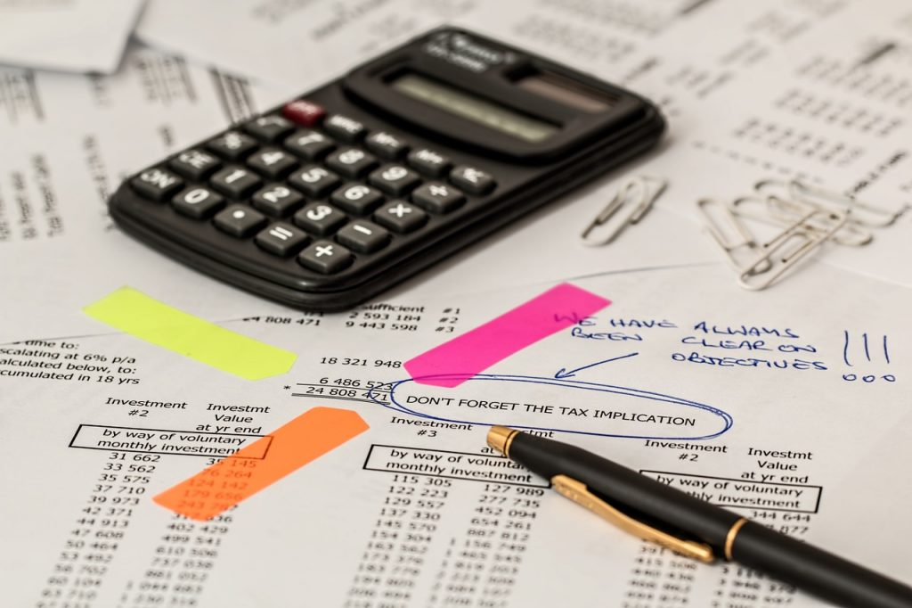 מחשבון ועט על מסמכי כפל ביטוחים